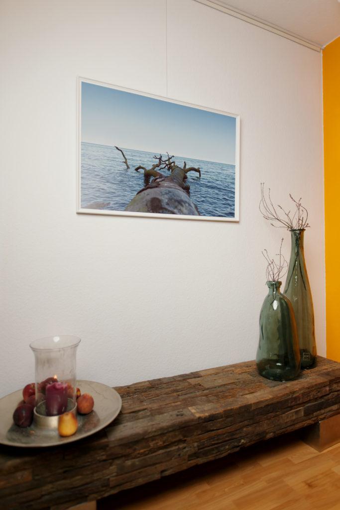 Eine Fotografie hängt im Flur der Praxis. Deko-Elemente stehen auf einer Bank.