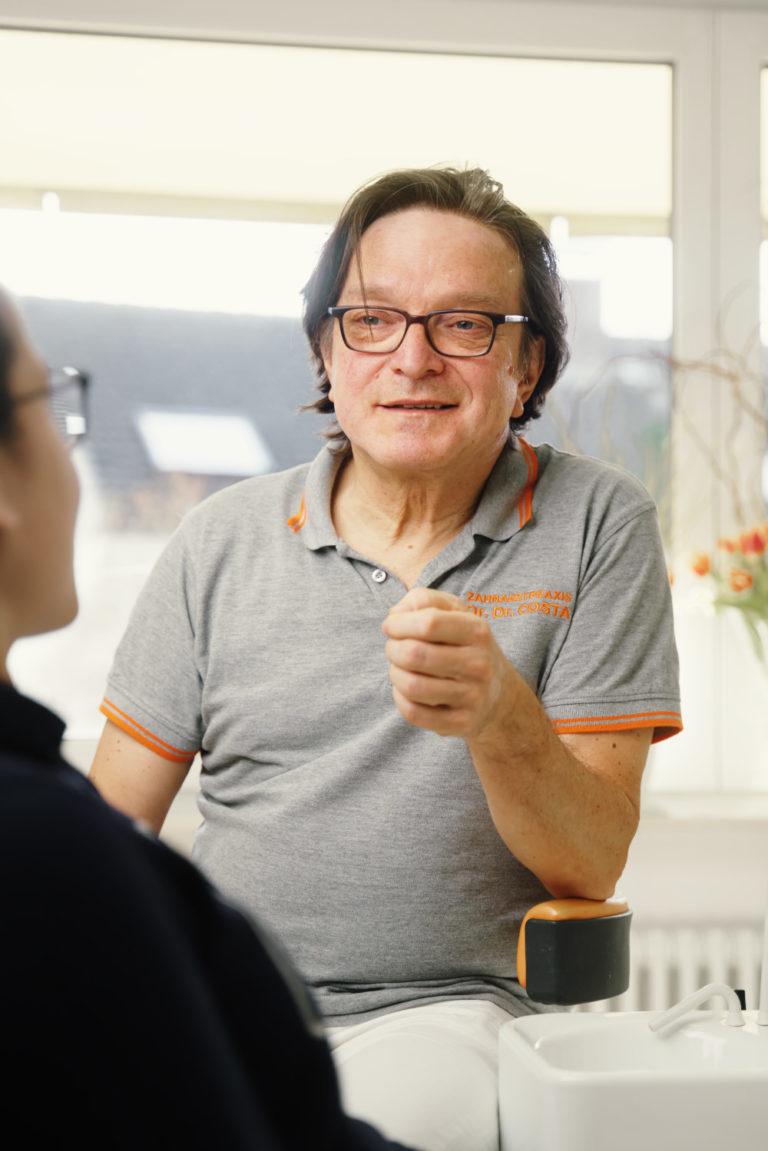 Dr. Dr. Dinu Costa im Gespräch während einer Behandlung.